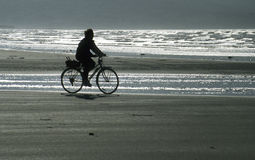Cyclist on beach at dawn Stock Images