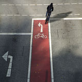 Cyclist from behind on a bike lane with symbol and arrow driving Royalty Free Stock Photography