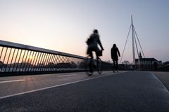 Cyclist on a bicycle bridge in Odense, Denmark stock photo