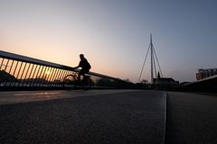 Cyclist on a bicycle bridge in Odense, Denmark stock images