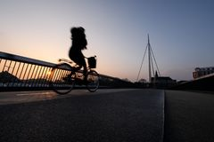 Cyclist on a bicycle bridge in Odense, Denmark royalty free stock image