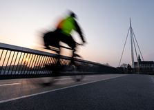 Cyclist on a bicycle bridge in Odense, Denmark stock image