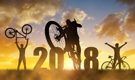 Cyclist with bicycle at sunset. New Year 2018 concept. Silhouette the cyclist with bicycle at sunset.Forward to the New Year 2018 Royalty Free Stock Photo