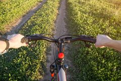 Cyclist on bike on field road. First person view. View from the first person of a cyclist riding on field country road in spring summer Royalty Free Stock Photography
