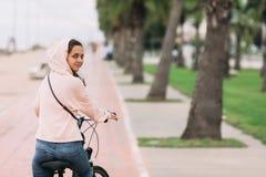 Cyclist on a bike path on the embankment. Woman cyclist riding a bike on bike path on the embankment stock photo