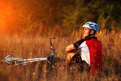 Cyclist with bike relax in the sunny autumn park Royalty Free Stock Photos