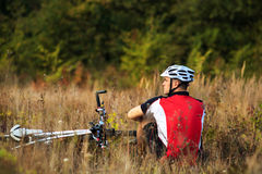 Cyclist with bike relax in the sunny autumn park Royalty Free Stock Photo
