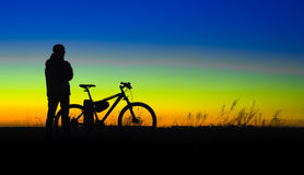 Cyclist with bike silhouette against sunset Royalty Free Stock Photo