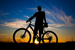 Cyclist with a bike silhouette on a blue sky Royalty Free Stock Photo