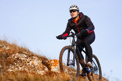 Cyclist in Black Jacket Riding the Bike on the Rocky Trail. Extreme Sport Concept. Space for Text. Stock Photos