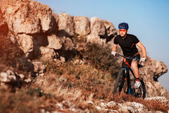 Cyclist in black sportwear Riding the Bike on the Rocky Trail. Extreme Sport Concept. Space for Text. Stock Images