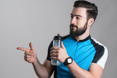 Cyclist in blue jersey shirt holding empty water container. Pointing at copyspace Stock Image