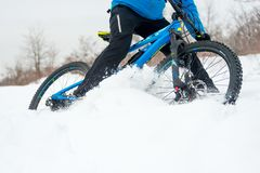 Cyclist in Blue Riding Mountain Bike on Rocky Winter Hill Covered with Snow. Extreme Sport and Enduro Biking Concept. royalty free stock images