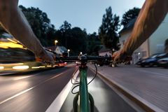 A cyclist and a bus on a street. First-person view of cyclist stock photo