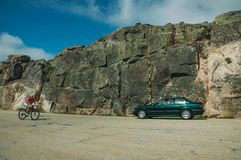 Cyclist and car on roadway in a rocky landscape. Serra da Estrela, Portugal - July 14, 2018. Cyclist and car on roadway passing through rocky landscape, at the stock images