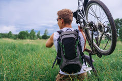 Cyclist carries bicycle in green meadow Royalty Free Stock Images
