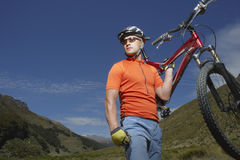Cyclist Carrying Bike Against Hills Stock Photography