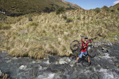 Cyclist Carrying Bike In River Stock Photography