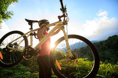Cyclist carrying mountain bike climbing on summer forest trail Stock Photography