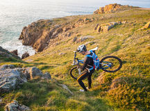 Cyclist carrying your bike on the Galician coast Stock Photos