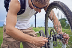 Cyclist checks brake wheel of bicycle Royalty Free Stock Photography