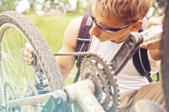 Cyclist checks chain of bicycle Stock Image