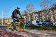 A cyclist in the city is moving along a bicycle path. Eco-friendly mode of transport. Bicycle with fixed speed Stock Images