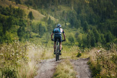 Cyclist coming down from the mountain top Royalty Free Stock Images