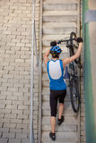 Cyclist coming up the steps with bicycle. Professional cyclist coming up the steps with bicycle royalty free stock image