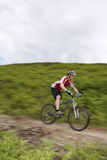 Cyclist On Countryside Track. Side view of a male cyclist on countryside track Stock Photo