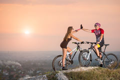 Cyclist couple with mountain bikes on the hill at sunset Royalty Free Stock Photo