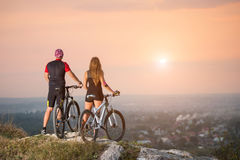 Cyclist couple with mountain bikes on the hill at sunset Stock Images