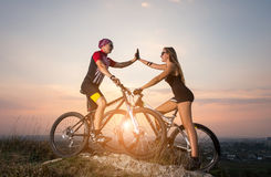 Cyclist couple with mountain bikes on the hill at sunset Stock Image