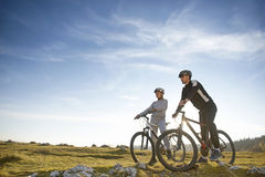 Cyclist couple with mountain bikes standing on the hill under the evening sky and enjoying bright sun at the sunset. Royalty Free Stock Images