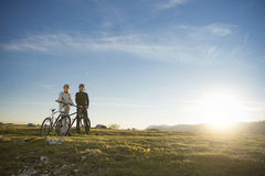 Cyclist couple with mountain bikes standing on the hill under the evening sky and enjoying bright sun at the sunset. Below is a city in the distance Royalty Free Stock Photography