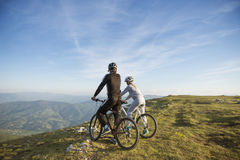 Cyclist couple with mountain bikes standing on the hill under the evening sky and enjoying bright sun at the sunset. Royalty Free Stock Photos