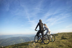 Cyclist couple with mountain bikes standing on the hill under the evening sky and enjoying bright sun at the sunset. Stock Photos