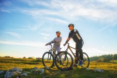 Cyclist couple with mountain bikes standing on the hill under the evening sky and enjoying bright sun at the sunset. stock photo
