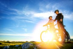 Cyclist couple with mountain bikes standing on the hill under the evening sky and enjoying bright sun at the sunset. royalty free stock photo