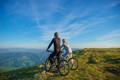 Cyclist couple with mountain bikes standing on the hill under the evening sky and enjoying bright sun at the sunset. Stock Images