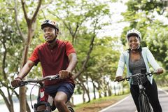 Cyclist couple riding together in a park royalty free stock images