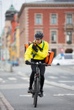Cyclist With Courier Bag Using Walkie-Talkie Stock Photography
