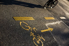 Cyclist on a crossing in a city casting a long shadow Royalty Free Stock Images