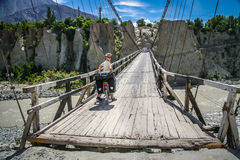 Cyclist crossing wooden bridge royalty free stock image