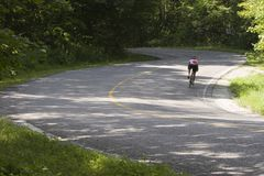 Cyclist on curve. Cyclist negotiating a twisty  country roadway Royalty Free Stock Photo