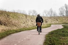 woman on a bicycle riding on a curved country road royalty free stock photos