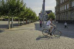 A cyclist cycling over a cobbled are in the city of Dusseldorf, Germany. A cyclist cycling over a cobbled are in the city of Dusseldorf, Germany stock photography