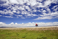 Cyclist cycling under the blue sky. A cyclist in red is cycling under the blue sky with white clouds Stock Photo