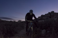 Cyclist descends the hill at night Stock Photography