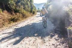 Cyclist on a dirt road in Guatemala highlands. Stock Photos